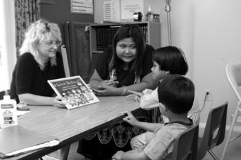 Aye Ma, Community Health Educator, acts as an interpreter for Cindy Barger, Parkview Speech Therapist, who is working to improve the communication skills of two local Burmese children at the Neighborhood Action Center located in Autumn Woods Apartments.